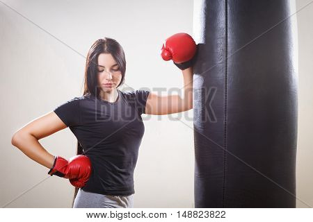 sports girl girl in boxing gloves and big punching bag