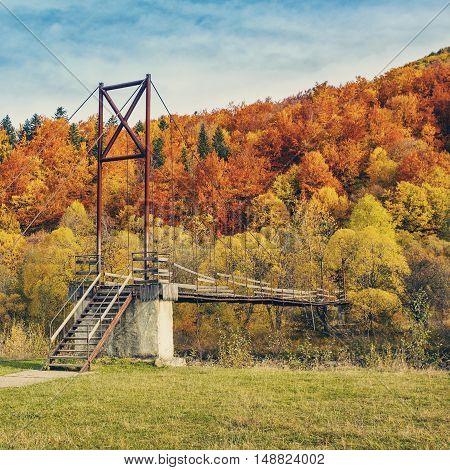 Suspension bridge in the autumn forest, autumntime