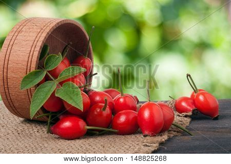 rosehips in wooden bowl on a wooden table with sacking and a blurred background.