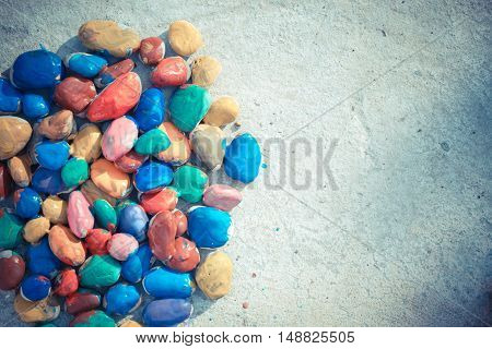 Colored stones colored paints in different colors lie on a flat surface. Second half empty. Close-up