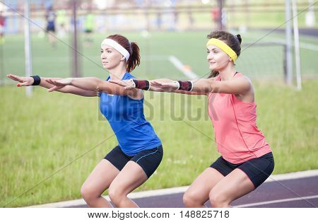 Sport Concepts and Ideas. Two Professional Female Athletes Having Training At Sport Venue Outdoors. Horizontal Image