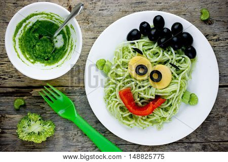 Pasta with green vegetables pesto shaped Frankenstein monster - healthy and creative baby breakfast or dinner on Halloween