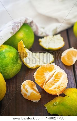 Fresh green peeled tangerines on wooden background