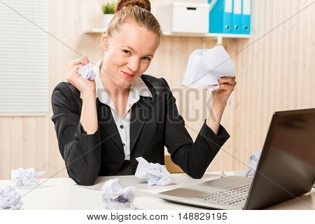 angry and aggressive businesswoman crumples documents in the office undergone stress