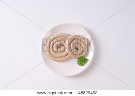 raw spiral pork sausages on white plate