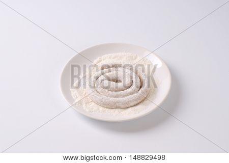 raw spiral pork sausage in flour