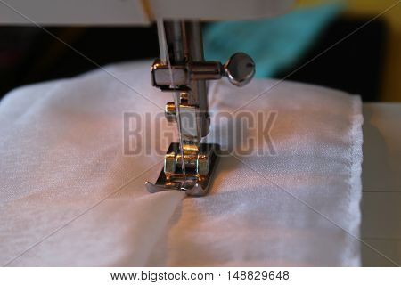 Sewing machine and white fabric - work process, close-up