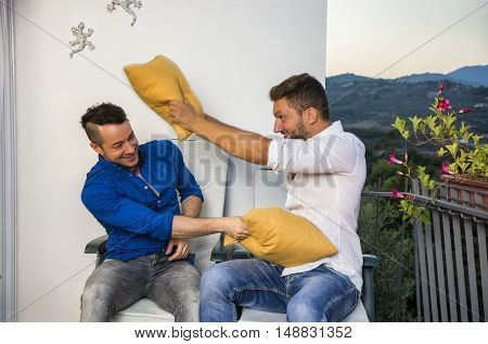Two handsome laughing men playing in pillow fight while sitting on chairs on balcony.