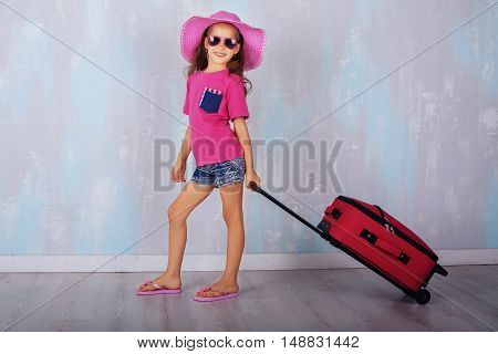flirtatious little girl carrying a suitcase. The concept of travel and lifestyle.