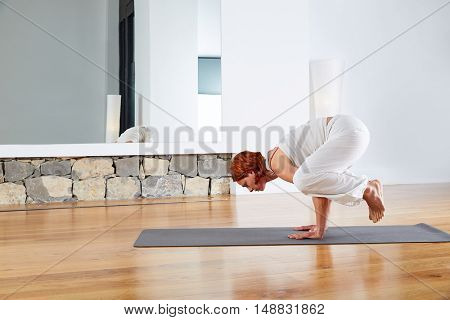 Yoga Crow Pose in wooden floor gym and mirror indoor
