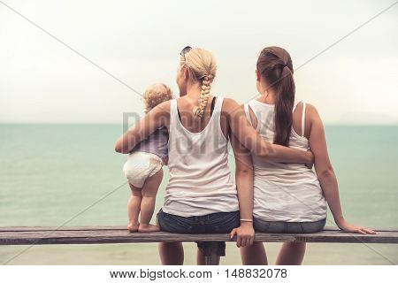 Loving mother embracing her children sitting on wooden bench at tropical beach during vacation. They together looking into the distance. Concept for togetherness and  bright future.