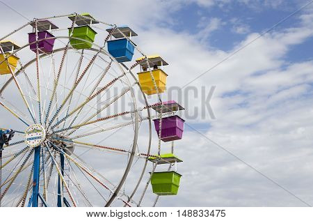 horizontal image of a part of a ferris wheel of different coloured seats against a beautiful blue sky with white clouds floating by.