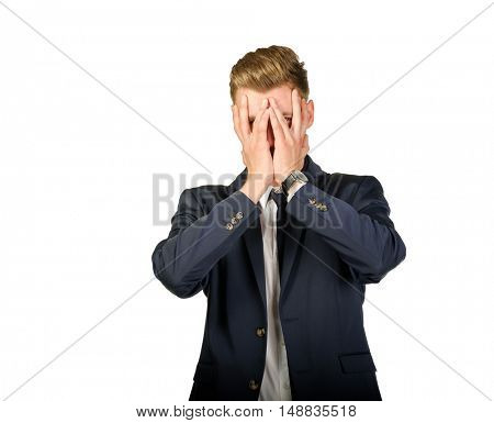 Young businessman in despair covers his face by hands. Crisis concept.
