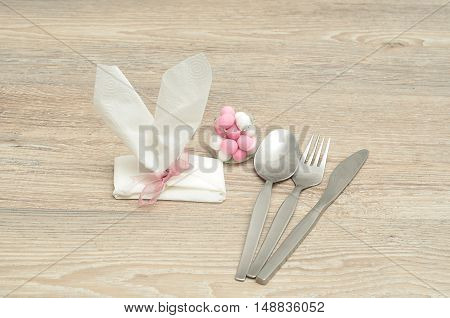 An Easter place setting with the napkin in the shape of bunny ears with a knife fork spoon and a bowl of candy displayed on a table