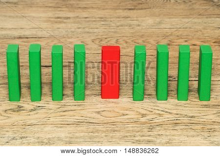 One red wooden block stands on the old wood table in the middle between the plurality of green blocks