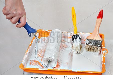 House painting supplies painter tools in an orange tray with white paint roller brush and paintbrushes.