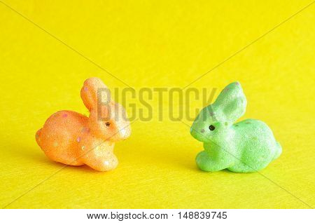 Two colorful bunnies used for decoration over the easter period isolated on a yellow background