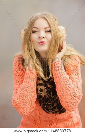 Happy fashion woman in studio blowing kiss. Glad attractive young girl in earmuffs sweater pullover and scarf. Happiness.