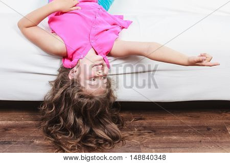 Little Girl Kid With Long Hair Upside Down On Sofa
