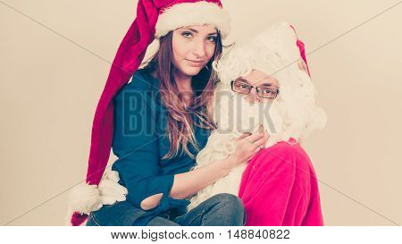 Xmas time people concept. Attractive lady with Santa Claus. Beautiful woman with red cap and blue outfit and Father Christmas carrying her.