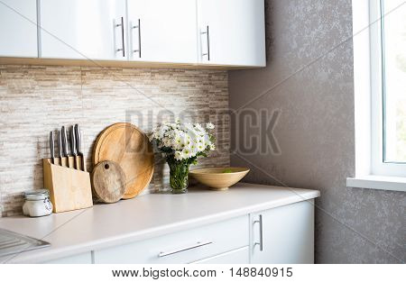 The interior of new bright white kitchen, home decor, furniture and utensils in a daylight
