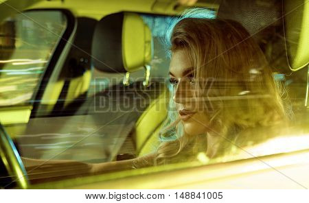 Attractive blonde beauty driving an elegant car