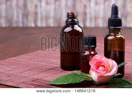 Pink rose essential oil bottles on brown backgroundselective focus