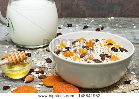 bowl of homemade muesli with honey dried fruits nuts and jug of milk on rustic wooden background. healthy breakfast