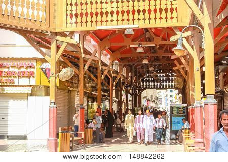 Dubai, United Arab Emirates - May 3, 2013: the entrance to the famous Gold Souk in Deira Dubai in the old Dubai Creek. Arabs and workers walking in traditional Souk.