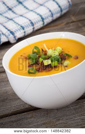 butternut squash soup topped with bacon and green onion on a wooden table