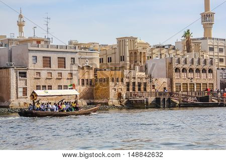 Dubai, United Arab Emirates - May 3, 2013: Deira old town and traditional Abra ferry along Dubai Creek.The creek divides the city into two main sections Deira and Bur Dubai.