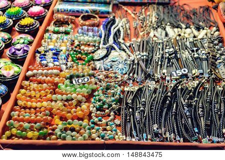 Rows of different leather braceletsnecklaces and other souvenirs at night market Koh Chang Thailand. Selective focus