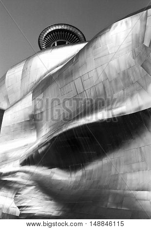 SEATTLE, UNITED STATES - APRIL 2, 2012: The rippled metal exterior walls of the Experience Music Project building, designed by Frank Gehry, in Seattle with the iconic top of the Space Needle appearing just over the top. (Scanned from black and white film.