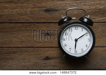 Retro alarm clock on wooden table, concept of time