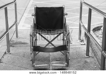 Empty wheelchair parked in hospital hallway, black and white