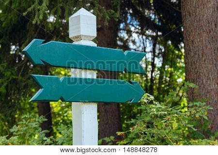 view of two wooden directional signs in forest