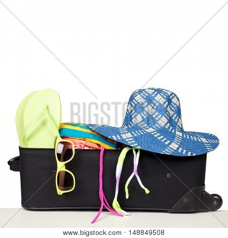 Suitcase with bikini and sunglasses.