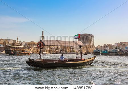 Dubai, UAE - May 3, 2013: Abra in Dubai Creek. The Creek divides the city in Deira and Bur Dubai. Abra is a traditional mode of transport between Deira and Bur Dubai.On background the skyline of Deira