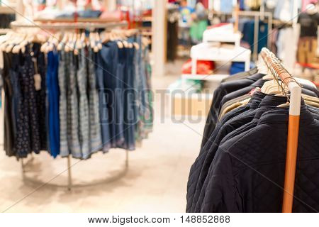 Dresses and jackets on hangers in a clothing store. Selective focus on clothes in foreground.