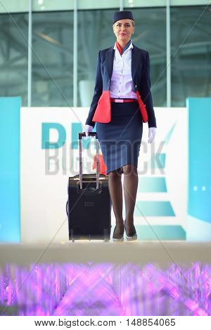 MOSCOW -?? JUL 09, 2015: A woman with suitcase shows a gray uniforms flight attendant at a special screening of uniforms airlines DME RUNVAY in Domodedovo