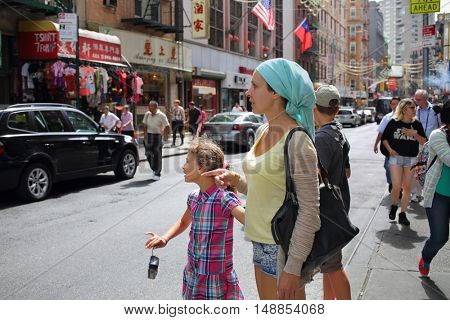 NEW YORK, USA - SEP 08, 2014: Woman with her son and daughter (with model release) walking on the Chinatown in New York