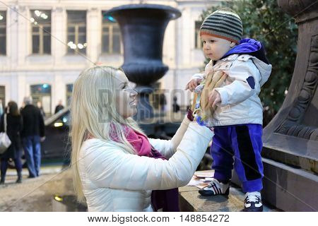 MOSCOW - SEP 5, 2015: Mother and little kid (with model releases) on walk in day of Moscow city in 2015, evening