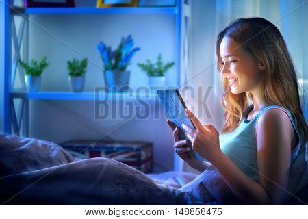 Beauty Girl using tablet pc in her bed at night. Beautiful young woman with tablet computer  lying in her comfortable bed in a dark room, watching movie, playing game, reading or chatting