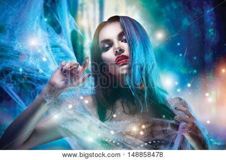 Beautiful Halloween Vampire Woman portrait. Beauty Vampire Vitch lady with blood on mouth posing in deep forest, wearing spider web. Fashion Art design. Sexy model girl with Halloween make up