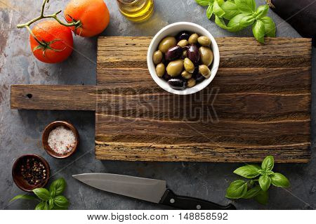 Colorful fruits and vegetables background overhead view of a cutting board with olives in a bowl