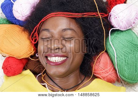 African Woman Surrounded By Balls Of Yarn.