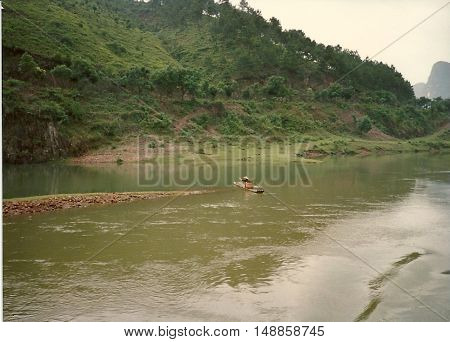 A man on a small raft on the Li River, between Yangshuo and Guilin, China, circa 1987.