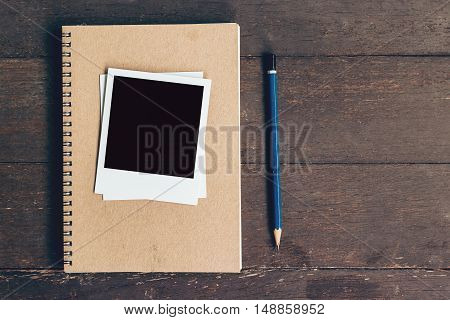 Notebook And Pencil With Frame Photo On Wood Table Background With Space