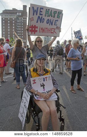 Asheville North Carolina USA: September 12 2016: Two woman one in a wheelchair hold protest signs at a Donald Trump campaign rally saying. One sign says