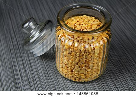 A jar of yellow lentils or Arhar daal in a jar on grey background selective focus.
